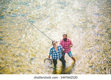 Father and boy fishing together. Brown trout fish. Fly angler on the river. Father and son relaxing together
