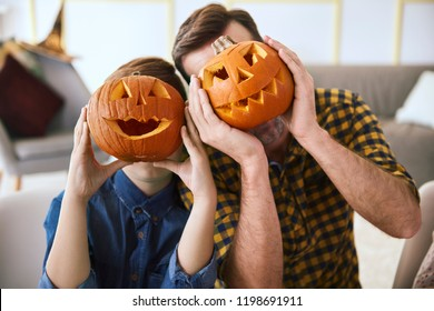 Father and boy with scary Halloween pumpkin