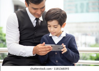 Father and Boy using Smartphone Together at Outdoor Place. People with Technology, Family, Education Concept.