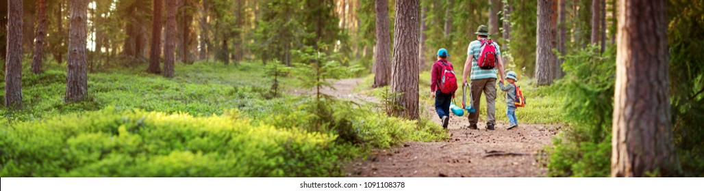 Father and boys going camping with tent in nature. Man with sons with backpacks walking in the forest