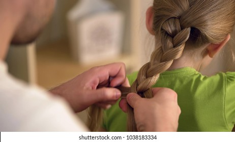 Father braiding daughters hair carefully, taking care of beloved kid, family