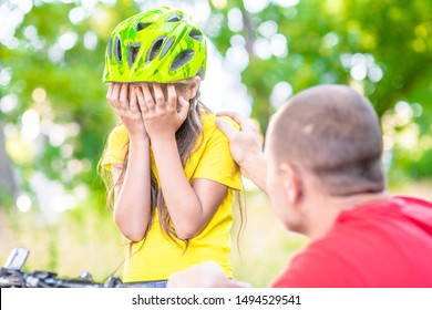 Father calms his sad daughter who did not get to ride a bike