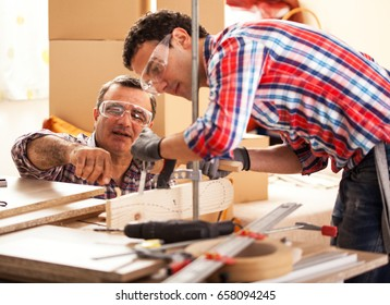 Father carpenter teaches his son how to use a chisel to shapes a wooden plank.