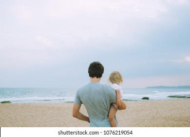 Father carries his daugher on the beach