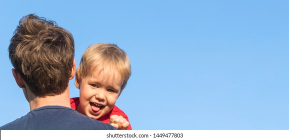 The father carries his son on his shoulder on background blue sky. Cheerful and funny little boy - blond looking at the camera and showing tongue. COPY SPACE.