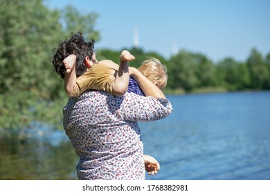 Father carries his son on the shoulder by the lake