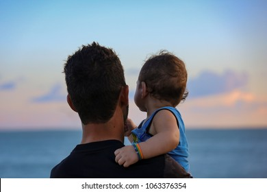 A father carries his son as they look out towards the horizon as the sun sets. Taken in Darwin, NT, Australia.