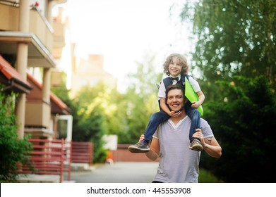 Father carries on his shoulders of his son-schoollboy. Little learner with one arm hugs dad for the neck and the other holding a folder . Boy's curly blond hair and a nice face. Father and son smile