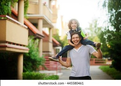 The father carries on his shoulders of his son-schoolboy. Little learner with one arm hugs dad for the neck and the other holding a green folder. Father and son smiling happily. Back to school.