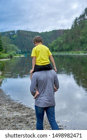 The father carries on his son's shoulders along the river bank, a view from the back. Summer rain, eco-tourism
