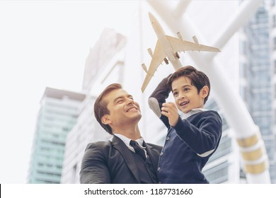 Father carries son playing  aviator toy air plane imagination dreaming of being a pilot future on business district urban , Dad and Son happy family concept