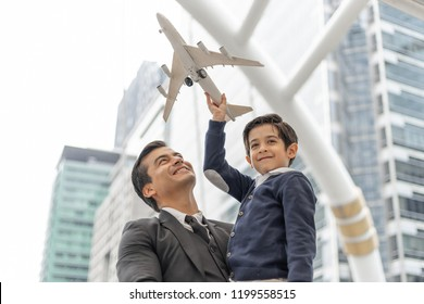 Father carries son playing aviator toy air plane imagination dreaming of being a pilot future on business district urban, Dad and Son happy family concept