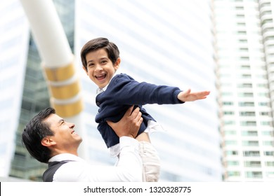 Father carries son playing aviator air plane imagination dreaming of being a pilot future on business district urban, Dad and Son happy family concept