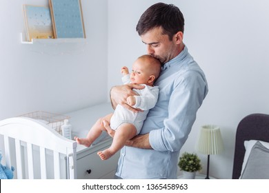 Father carrying baby son in bed room
