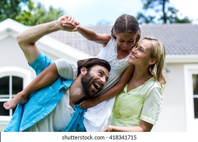 Father carrying daughter on shoulder besides woman in yard