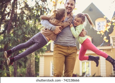 Father carrying daughters around neck.