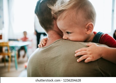 Father carrying his son into a classroom
