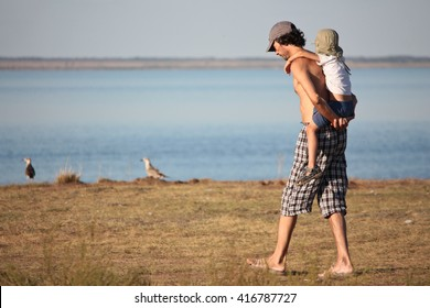 father carrying his son on his back by the lake shore