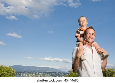 Father carrying his son on piggy back ride outdoors against nature and blue sky