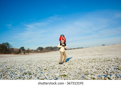 Father carrying his son piggyback. view from the back. Baby Boy Son On The Shoulders Of Dad in the winter. happy family with the sky on background