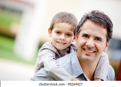 Father carrying his son and smiling - outdoors