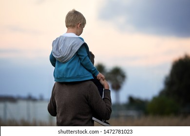 Father carrying kid on his back, child sitting on dads shoulders quality family time outdoors