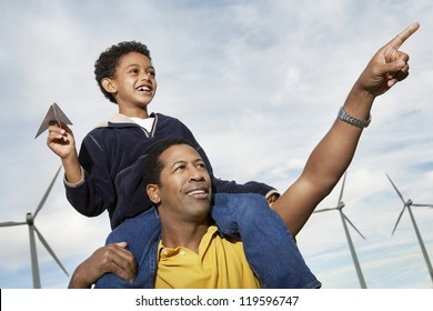 Father carrying son on shoulders while pointing at wind farm
