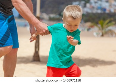 Father is catching little baby boy on sandy beach who disobey, protests and want to escape, naughty son during family vacation