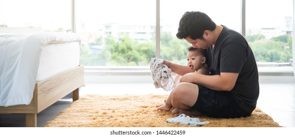Father change 8 months old son's cloth in bed room, image with copyspace