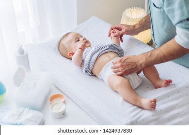 Father change diapers to baby boy on baby changing table