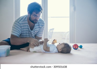 Father Changing Diaper To His Son