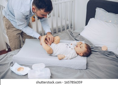 Father changing diapers to baby son on changing mat