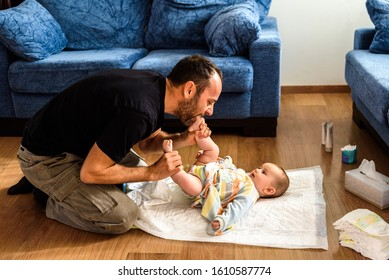 Father changing his daughter's dirty diaper on the living room floor.