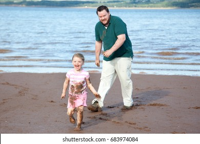 A father chasing his cheerful daughter on a muddy beach.