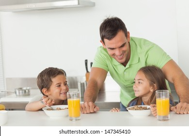 Father chatting to his children while they are having breakfast in the kitchen