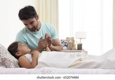 Father checking temperature of sick daughter