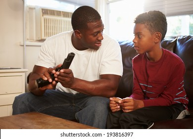 Father Checks Gun As Son Sits Next To Him On Sofa