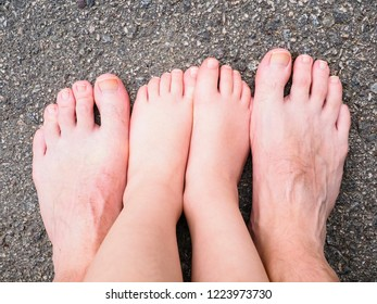 Father and child barefoot on dry asphalt in daylight at summer