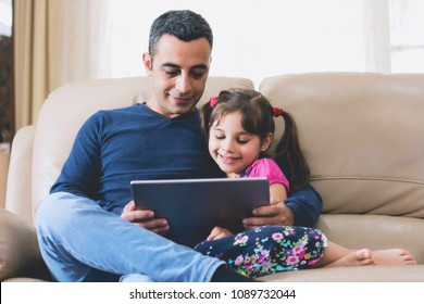 Father and Child Daughter Looking At Digital Tablet Screen Together