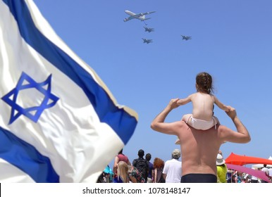 Father with child daughter on shoulders by sea beach watch on military aircrafts at festive air parade of Israel Army of Defense. Israeli National flag waving on Independence Day of Israel