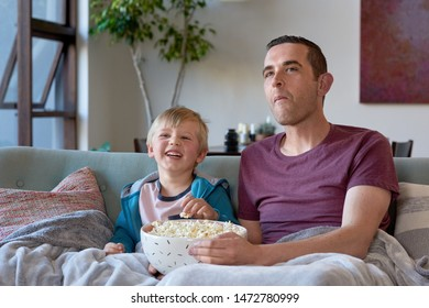 Father and child eating popcorn and watching cartoon movies together family bonding leisure activity
