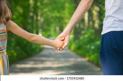 Father and child go holding hand. Selective focus. nature.