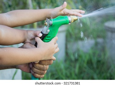 Father and child hand help watering plant in garden,selective focus