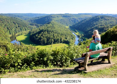 Father and child hiking and enjoying view from famous panoramic point of The Giant's tomb of the river Semois, located nearby the city of Bouillon, Wallonia, Ardennes, Belgium.