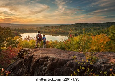 father and child hiking to  the top of a mountain to enjoy the view at sunset