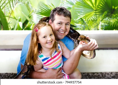 Father and child hold and feed huge python snake at day trip to zoo. Dad and kid watching wild animals in terrarium. Little girl holding snakes. Wildlife safari park for children. Kids with reptiles.