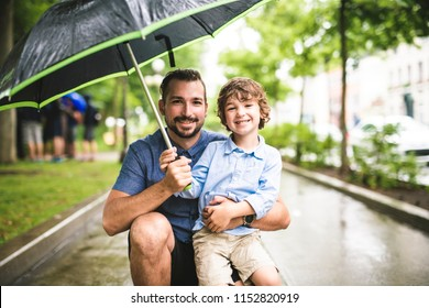 Father and child on a rainy day in a park with umbrella