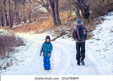 Father and child on a winter walk in nature