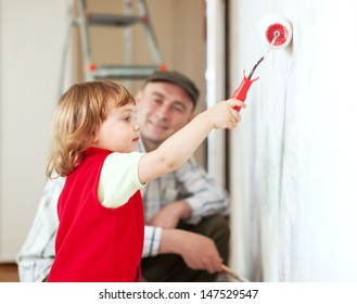 father with child paints wall  at home