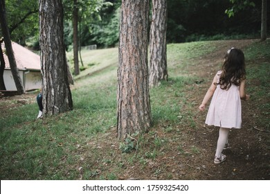 Father and child playing hide and seek in park. Man hiding behind tree while little girl is looking for him.